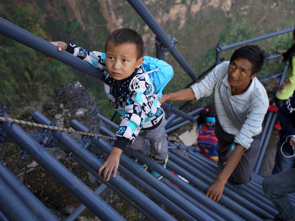 鉄製のはしごをのぼる子ども