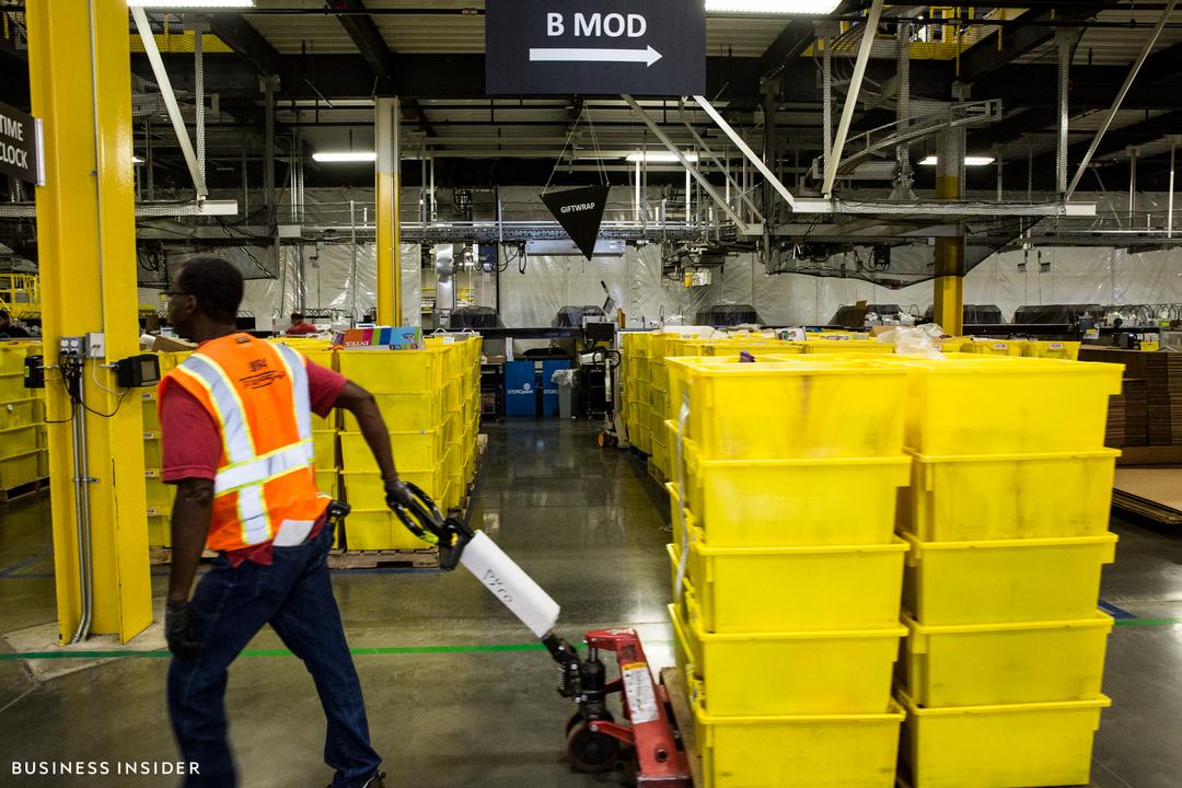 配送品が入った黄色のボックスを、台車に載せて運ぶ男性