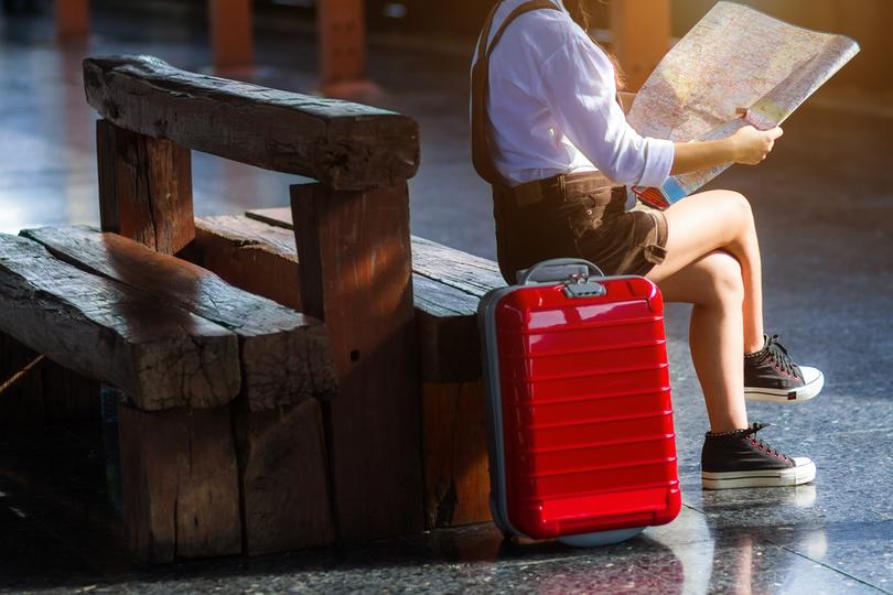 スーツケースを傍らに、地図を広げる女性