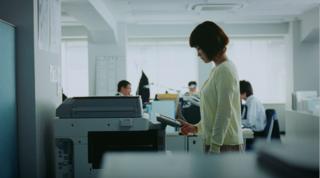 コピー機の前でたたずむ女性