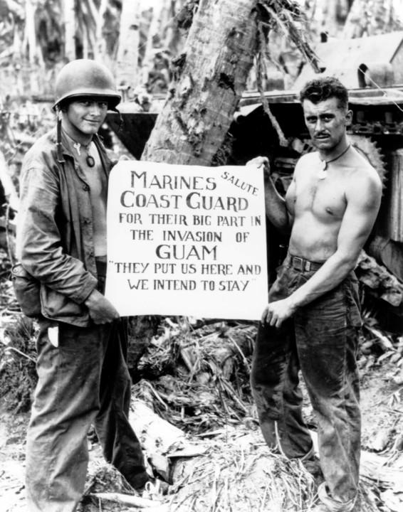 アメリカ軍兵士2人がグアム奪還記念のメッセージを掲げている写真