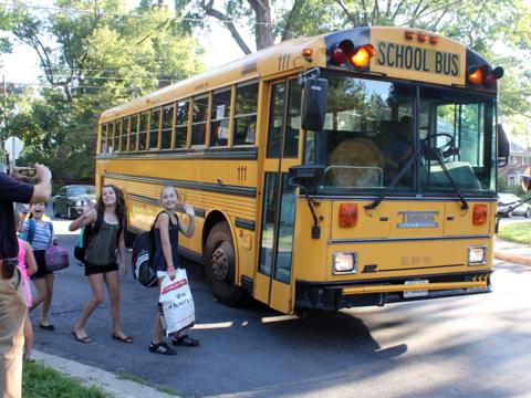 スクールバスの前で写真を撮る光景