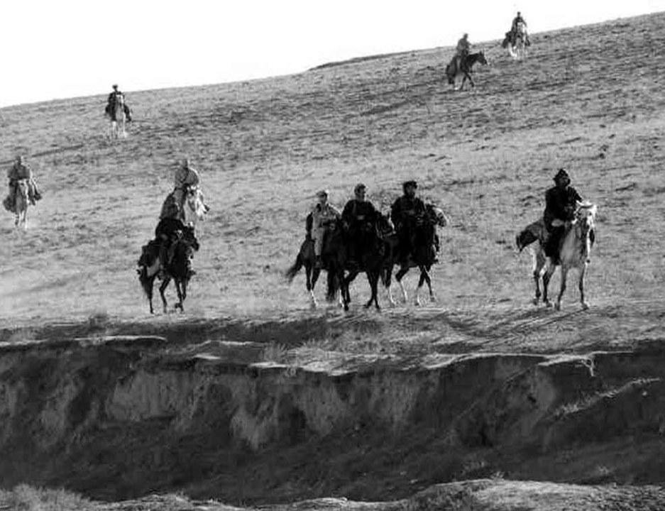 馬に乗って荒野を行く人々