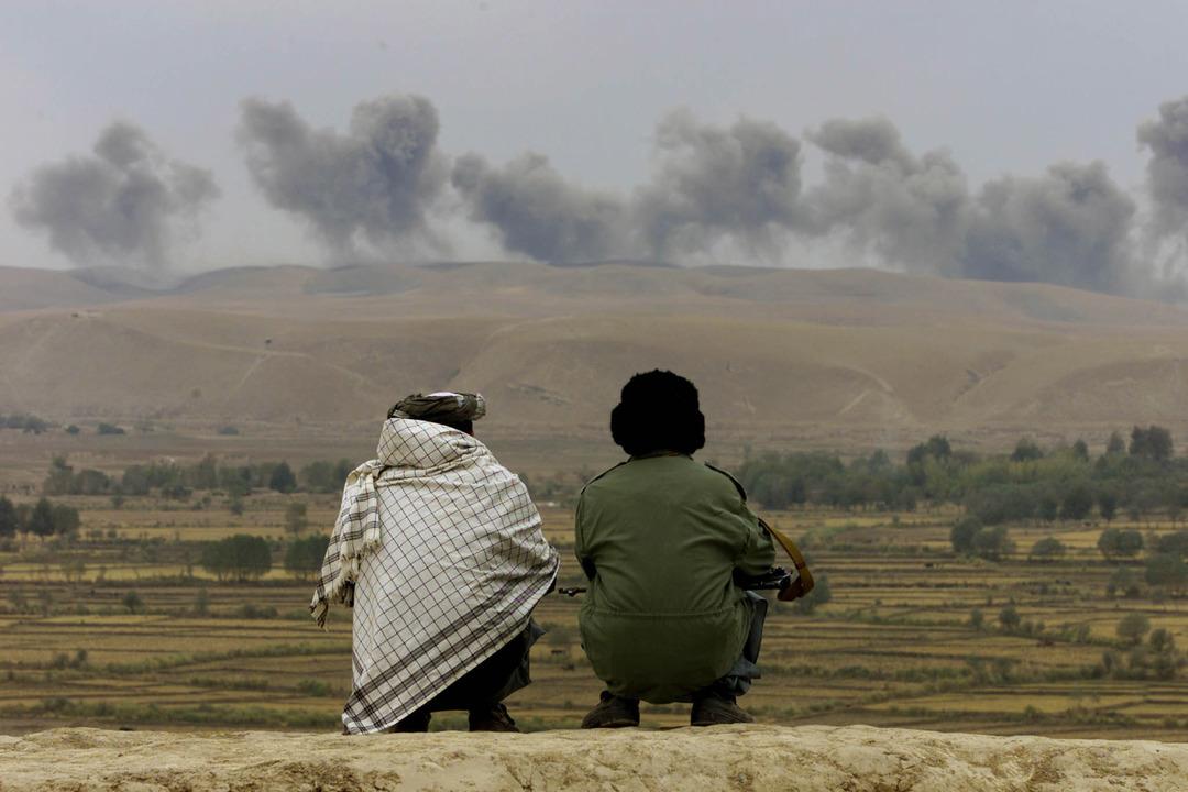 立ちのぼる土埃や煙を眺める北部同盟の兵士たち