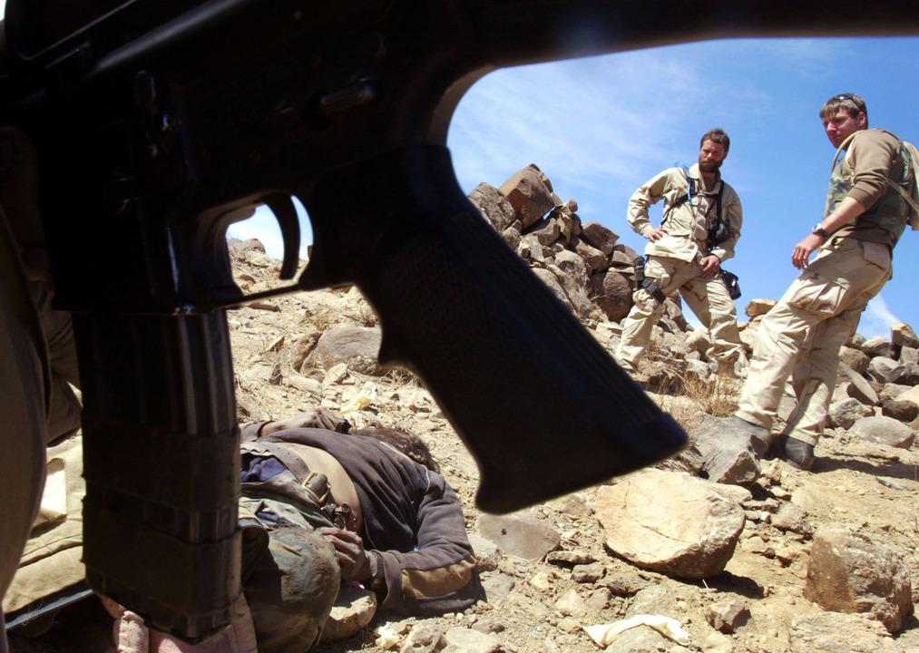 アルカイダもしくはタリバンの兵士の遺体と、その横を通り過ぎる米兵たち