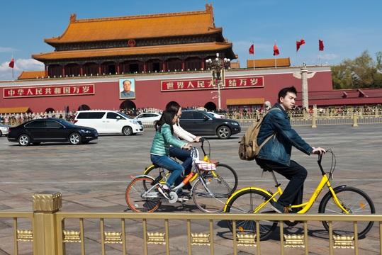 シェア自転車に乗って天安門広場を横切る人々
