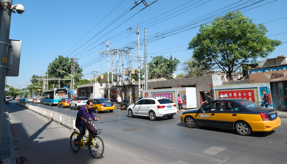 渋滞中の道路脇を自転車に乗って通り過ぎる男性。