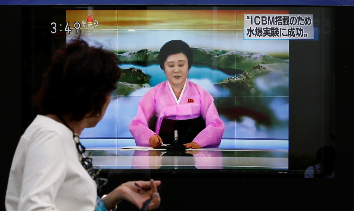北朝鮮による核実験のニュースが映し出された街頭モニターの前を通り過ぎる人