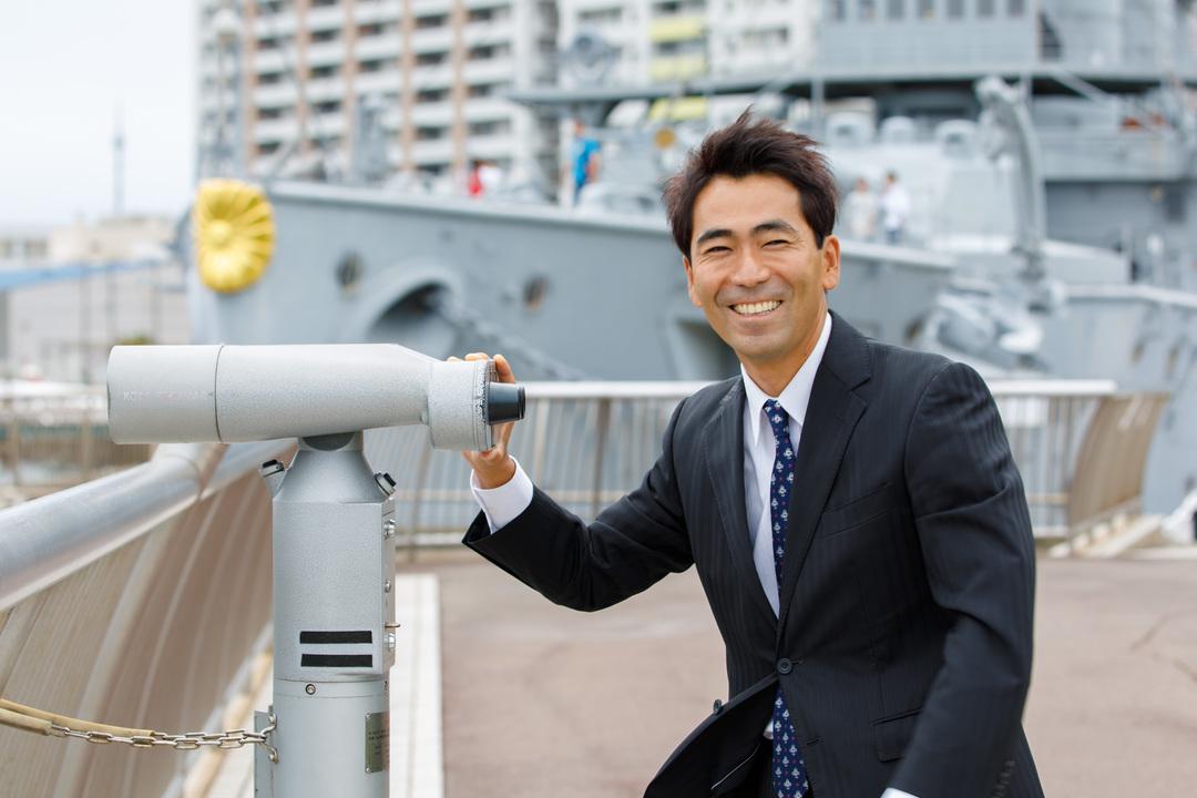 軍艦をバックに写る吉田氏