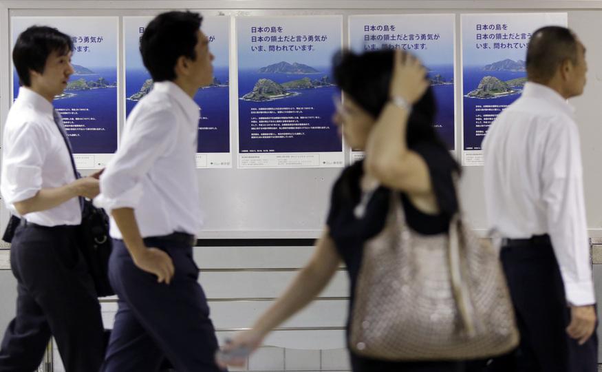 東京都が尖閣諸島購入計画のために作成したポスターの前を通り過ぎる人々