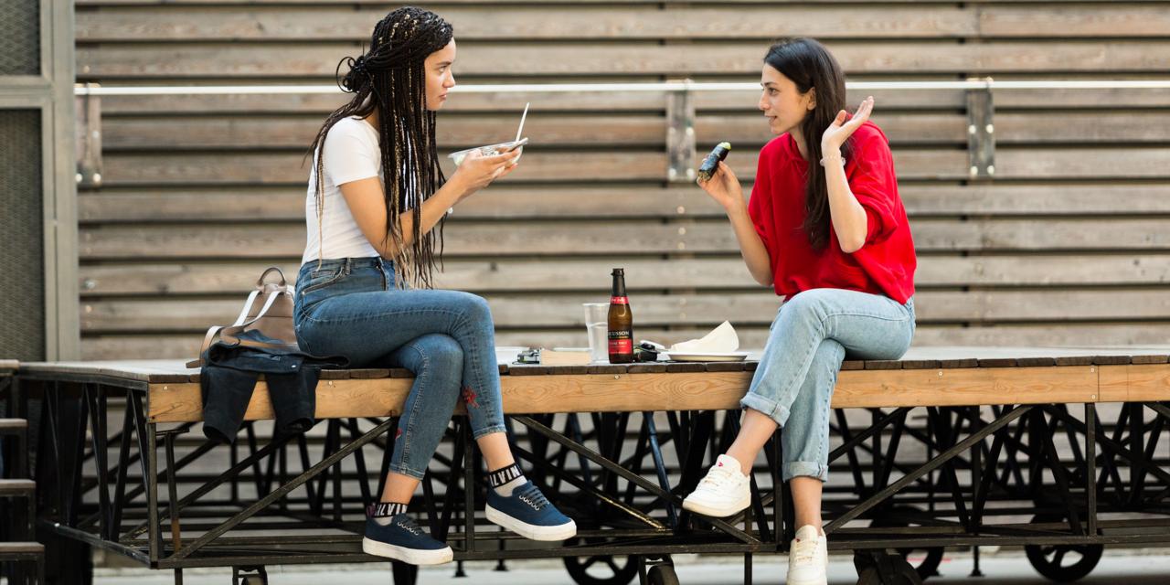 ベンチに腰を掛け食事をする女性たち