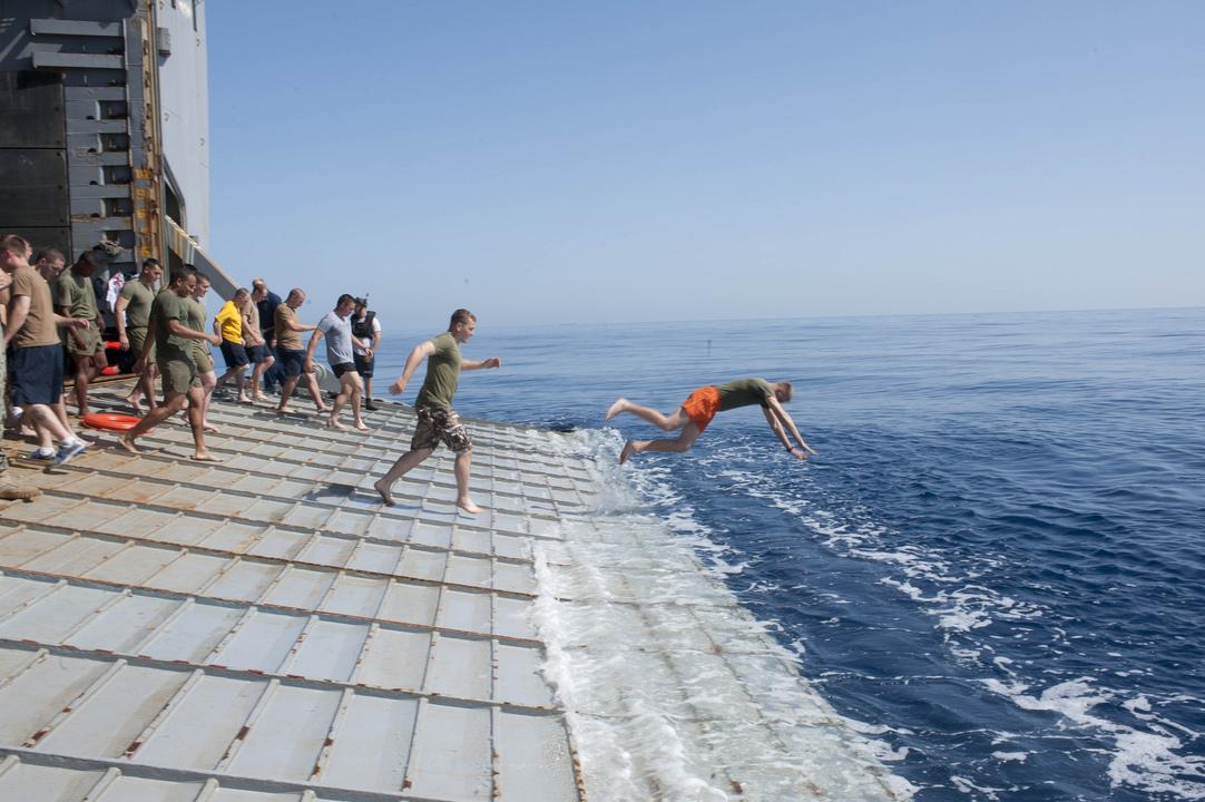 ドック型揚陸艦フォート・マクヘンリーの船尾から地中海へジャンプする海軍兵と海兵隊員たち