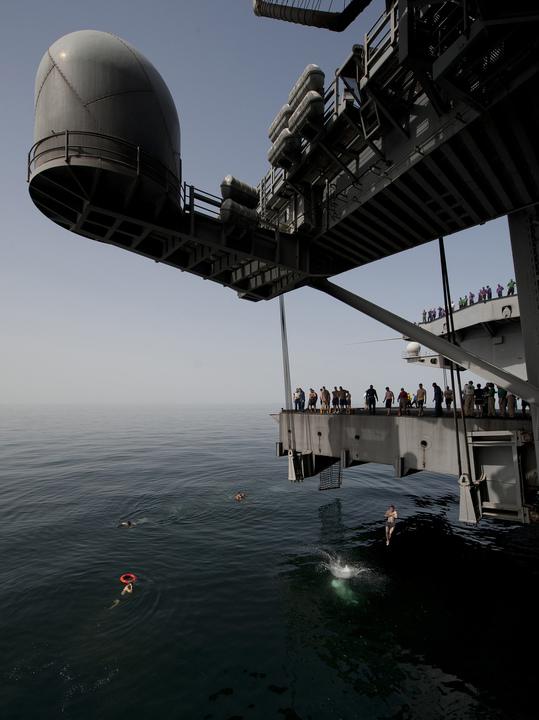 ニミッツ級航空母艦カール・ヴィンソンの航空機用エレベーターからアラビア海ジャンプする海軍兵たち