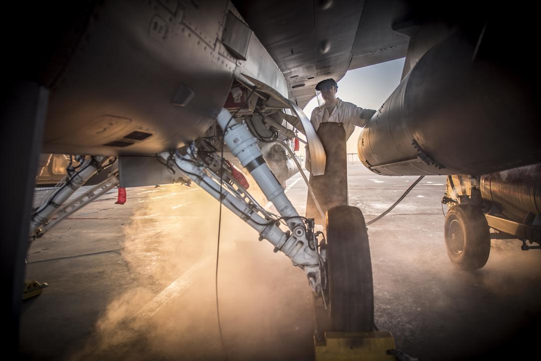 液体酸素のホースをF-16につなぐ兵士
