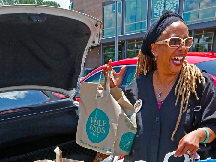 ホールフーズのエコバッグを持つ女性