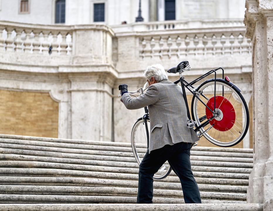 自転車を担いで階段を上る男性