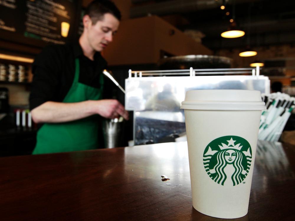スターバックスの店員と紙コップに入ったコーヒー