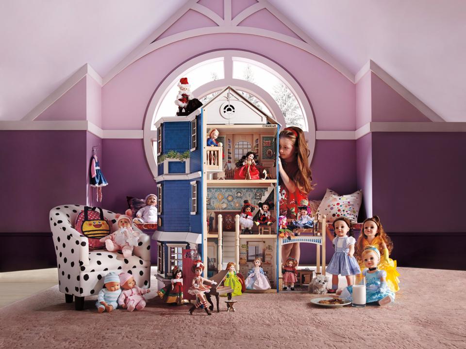 人形とドールハウスで遊ぶ少女