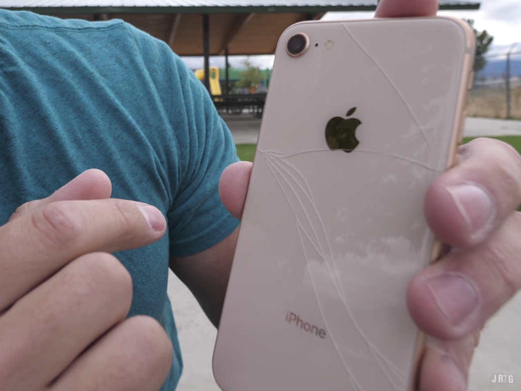 割れたiPhone 8の背面を見せるザック氏