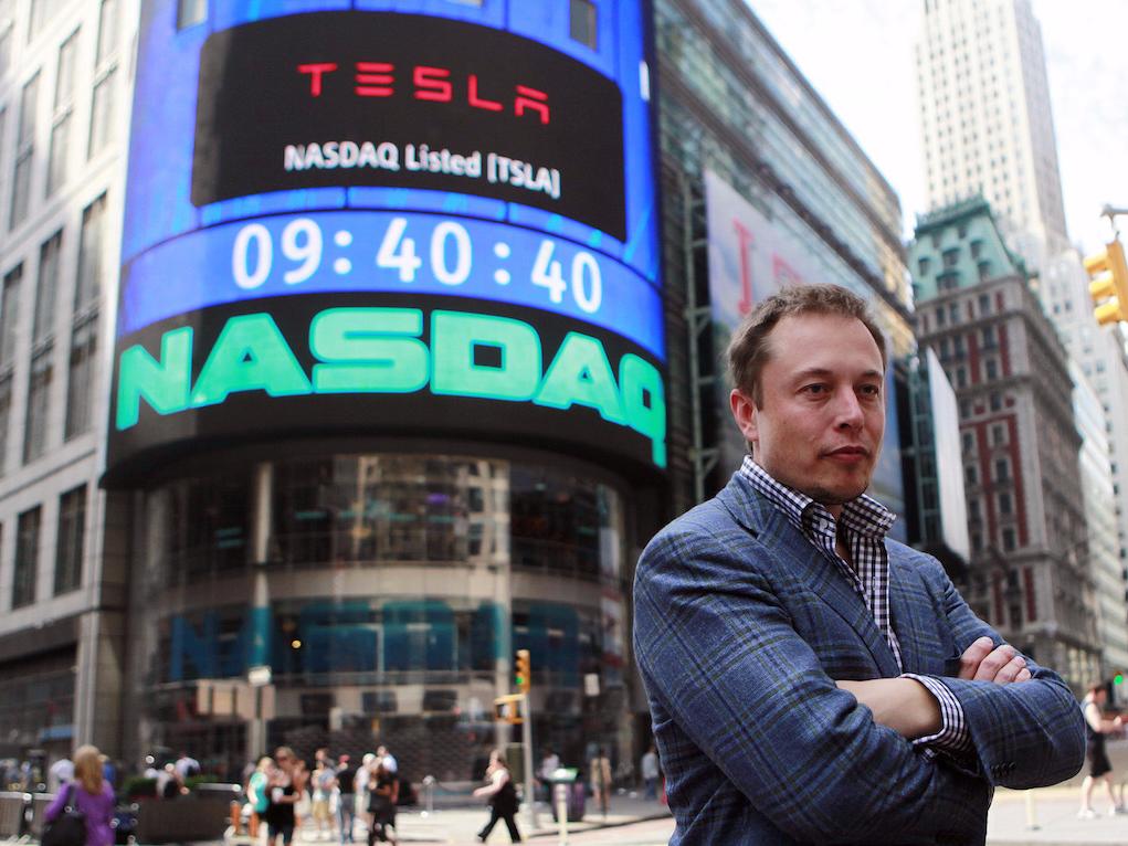 NASDAQの前で腕組みをするイーロン・マスク氏