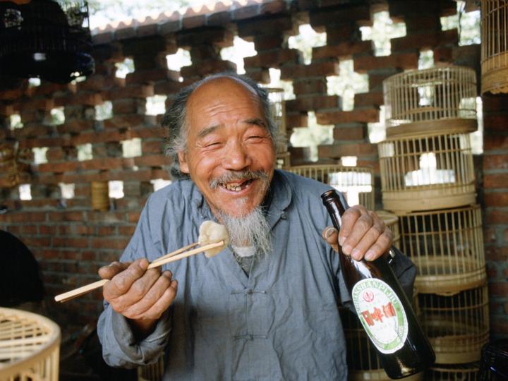 お酒と食事を楽しむ老人
