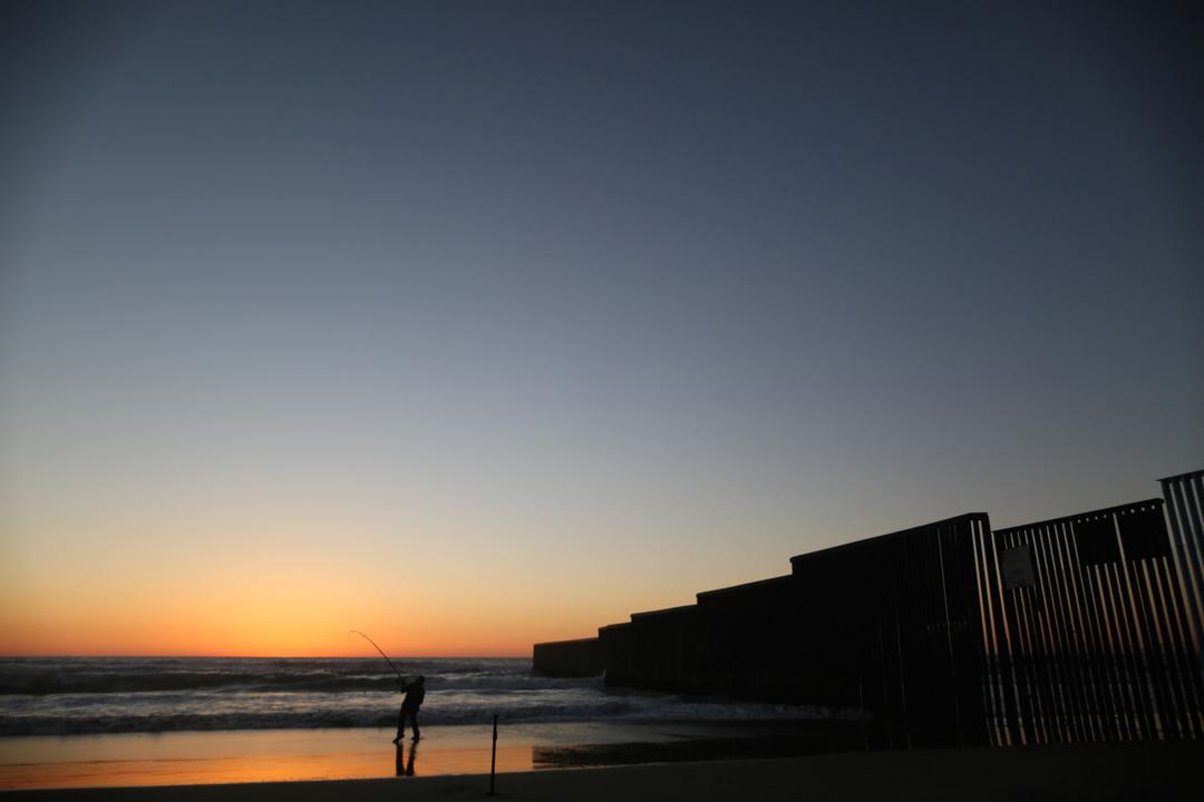 国境付近で夕暮れ時に釣りをする男性