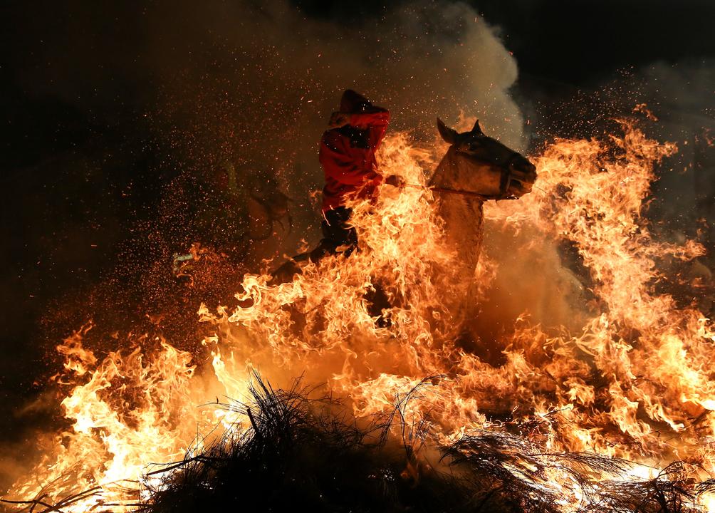 炎の中を馬に乗って駆け抜ける人