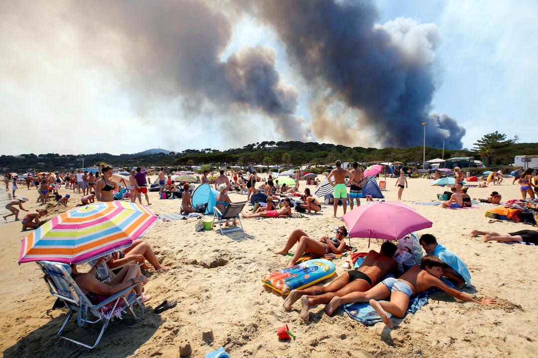 燃える丘を見つめる観光客