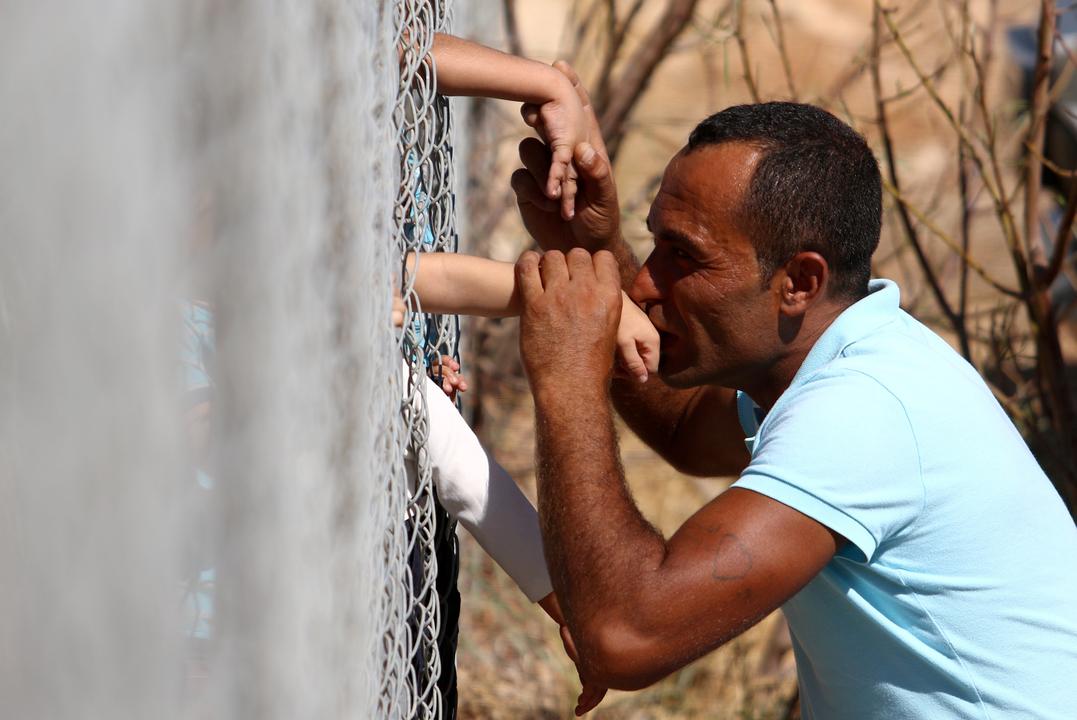 フェンス越しに子どもの手にキスをする男性