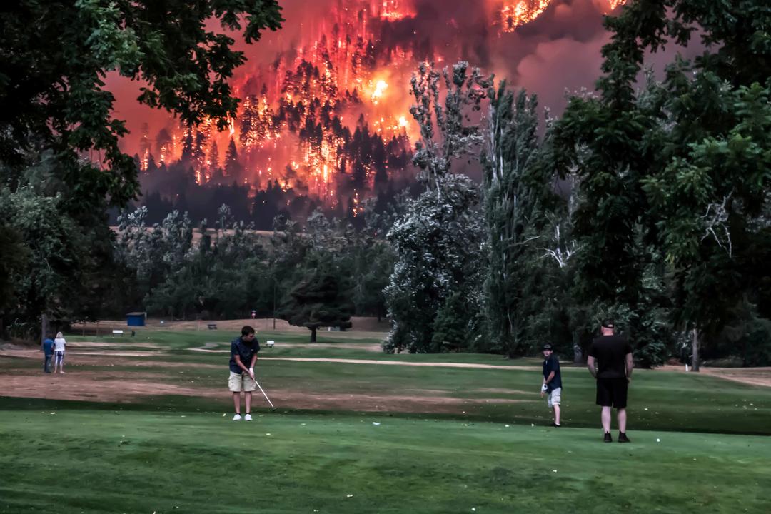 山火事の前でゴルフをする人たち