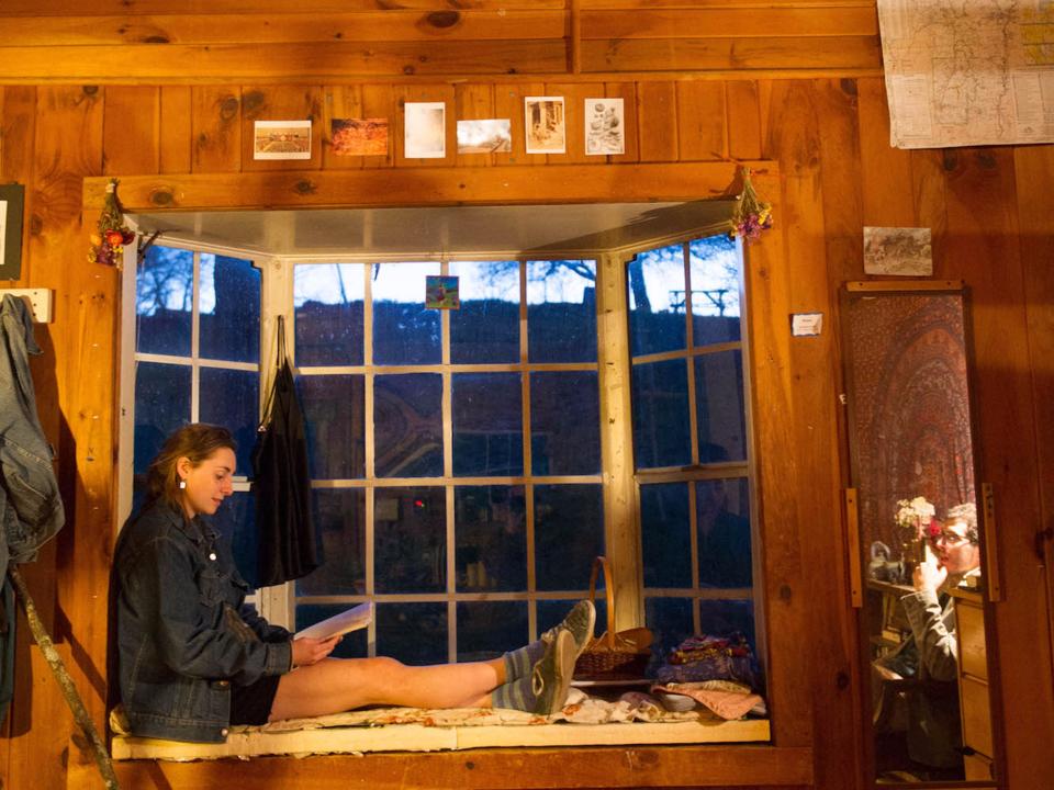 木造の小屋で読書する生徒