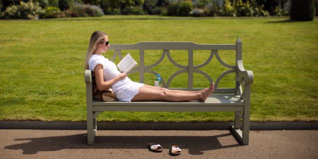 公園のベンチに寝そべって本を読む女性