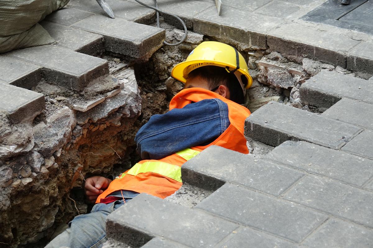 道端の溝の中で休む建設作業員