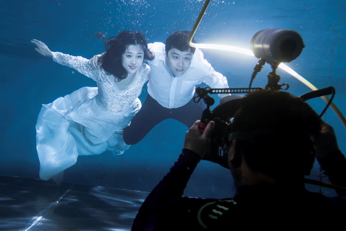 プールの中で結婚写真を撮影するカップル
