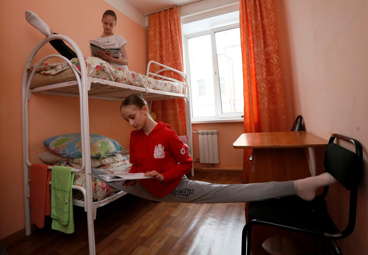 勉強をしながら、柔軟体操をする女子学生