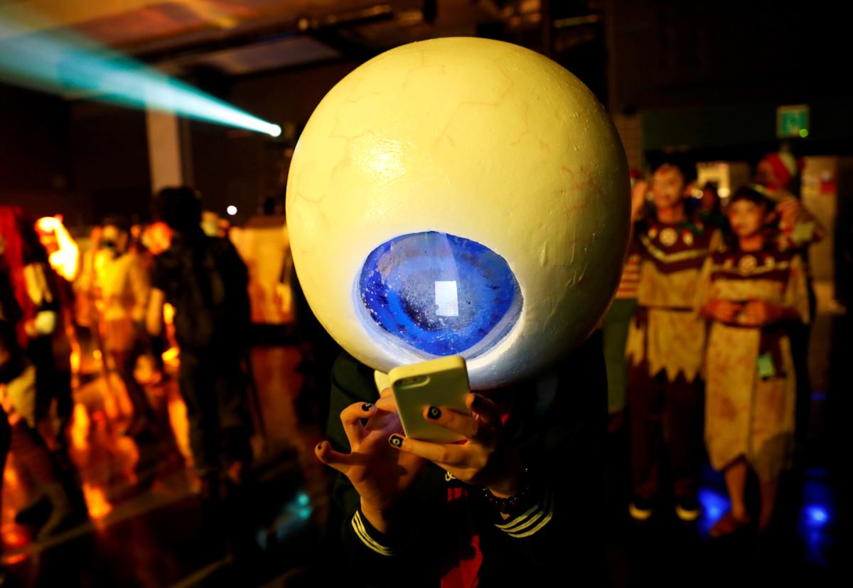 川崎で開かれたハロウィン・イベントで、スマートフォンを使う参加者