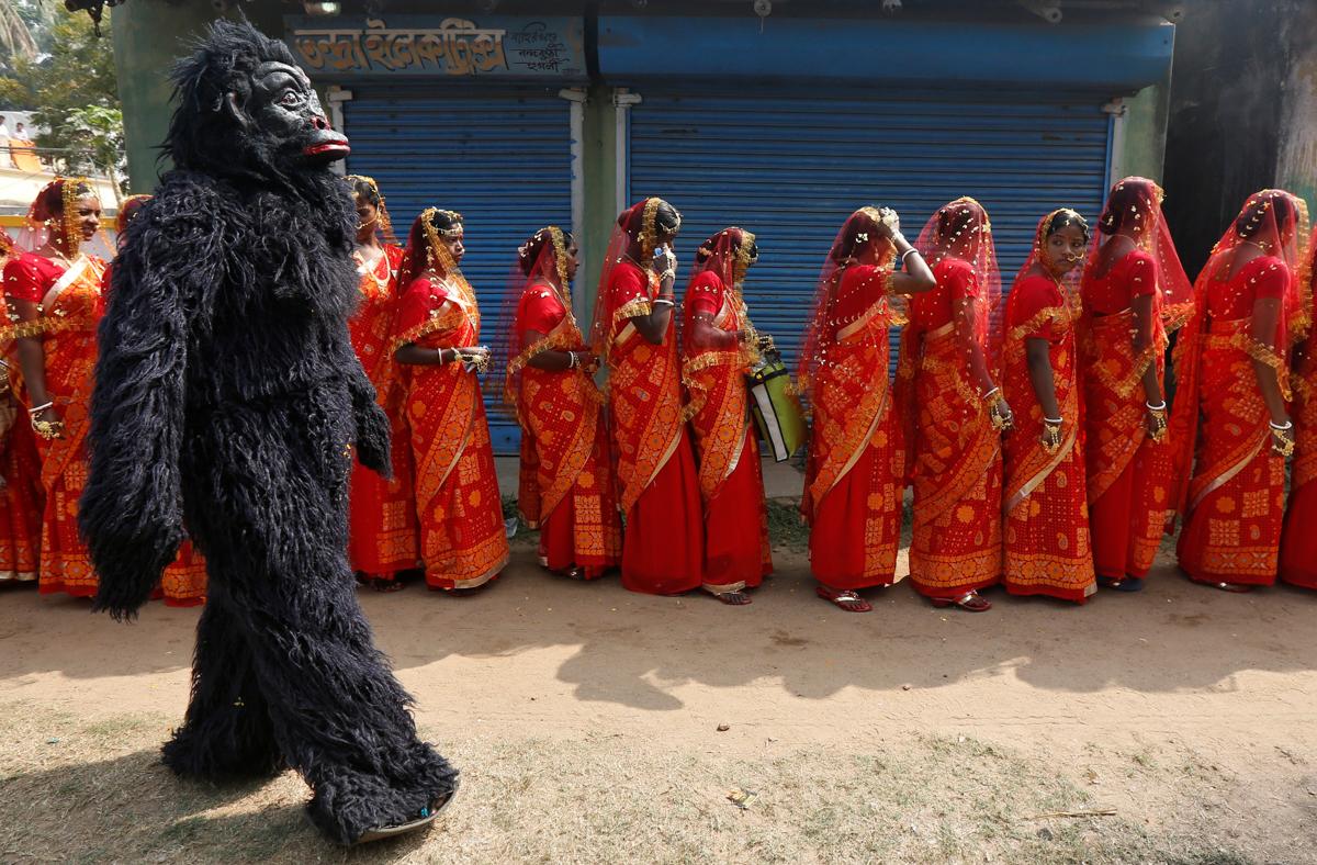 集団結婚式に参加する花嫁たちの隣を歩くチンパンジーの着ぐるみ