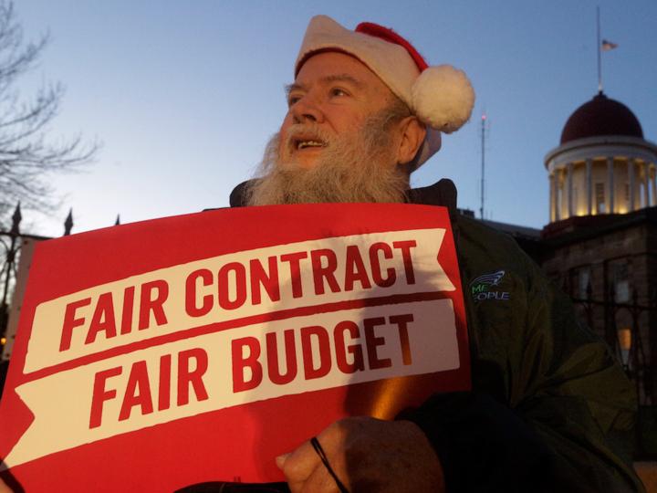 「FAIR CONTRACT/FAIR BUDGET(公正な契約、公正な割り当てを)」のボードを掲げる男性
