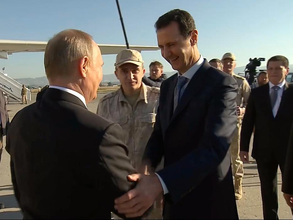 握手をするシリアのアサド大統領とロシアのプーチン大統領