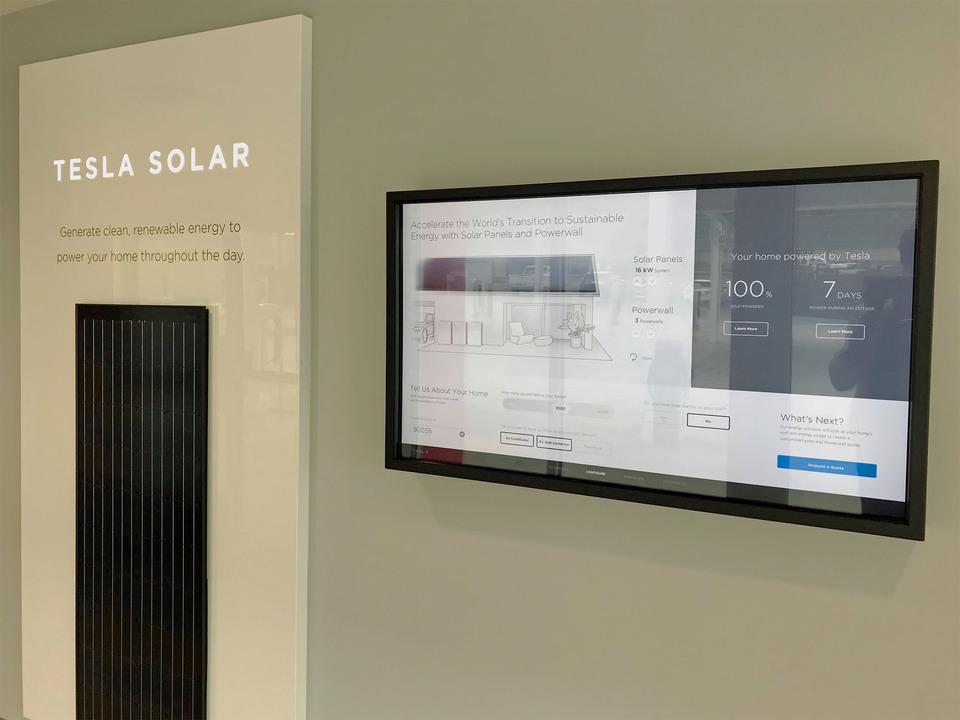 テスラ・ソーラーの展示品と大画面ディスプレーに表示される概算
