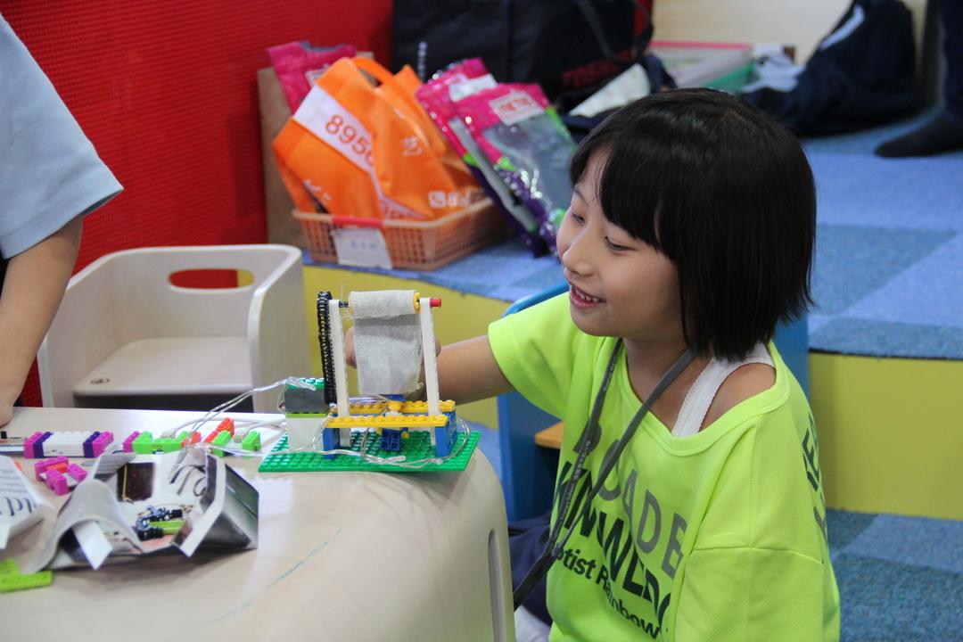 レゴのようなブロックとマグネット式の電子回路(工作キット「LittleBits」のようなもの)を組み合わせた製品「METAS」でものづくりをする子ども。