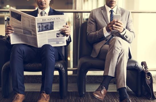 ホームで読書するビジネスパーソン