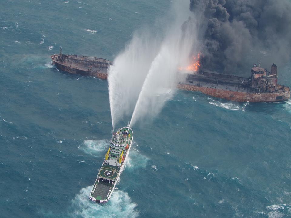 炎上するタンカーと消火を試みる船