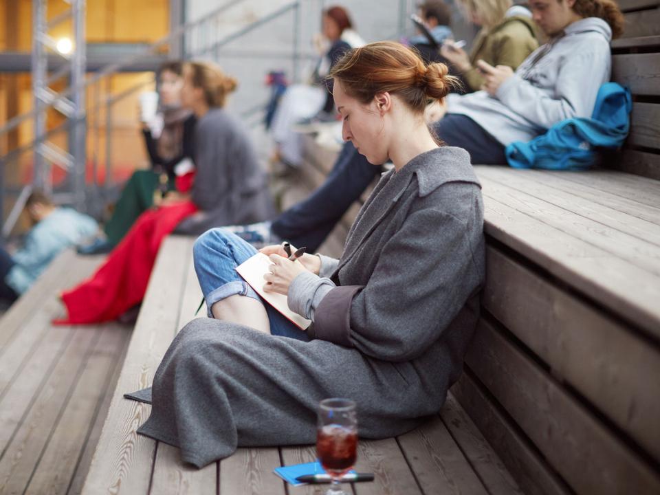 座りながら手帳をのぞき込む女性