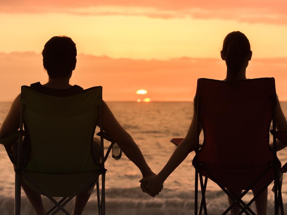 手を繋いで夕日を見る男女