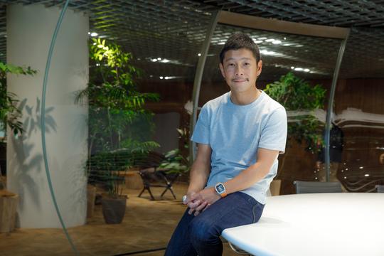 前澤氏がテーブルに腰掛けて微笑む。
