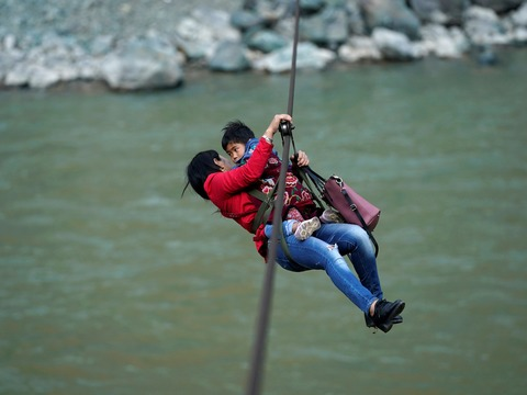 ジップラインで川を渡る親子