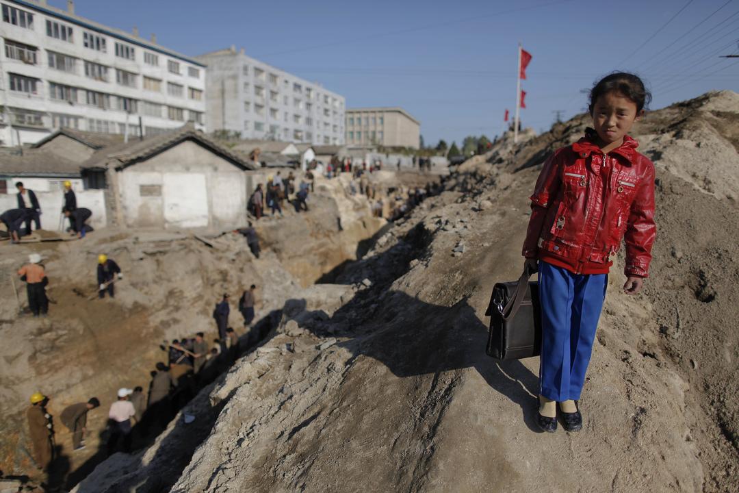 工事現場のすぐ近くを歩く少女