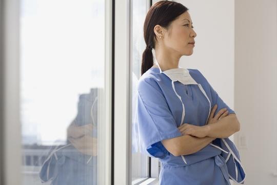 窓際で腕を組む女性医師