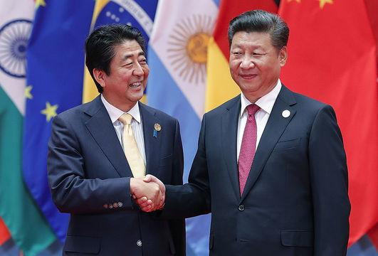 握手を交わす安倍首相と習近平国家主席